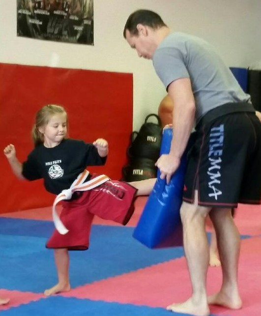 Little Dragon kicking Mike Price while learning Martial Arts